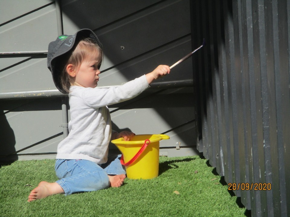 little girl painting wall